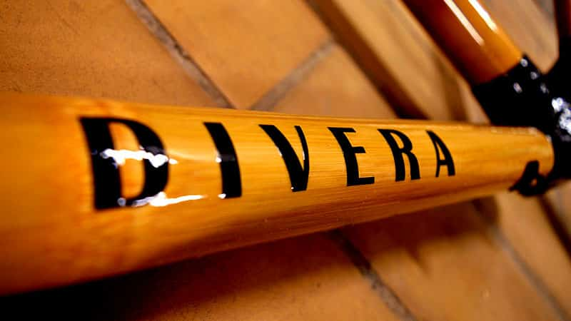 Divera text written on a piece of bamboo that is part of a bicycle frame